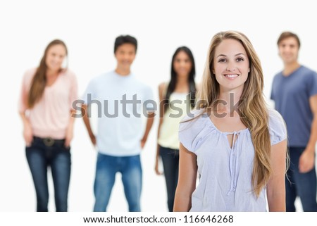 People smiling with one woman in foreground against white background