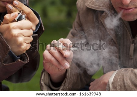 People smoking maijuana from a pipe - stock photo