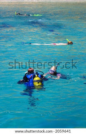 People snorkeling and some scuba diving in clear turquoise water.