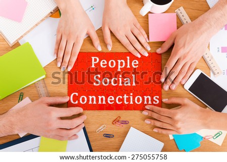 People social connections. Top view close-up image of people touching jigsaw puzzle with social connection text on it  - stock photo
