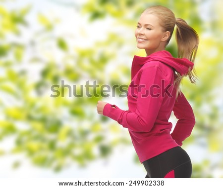 people, sport, fitness and slimming concept - happy woman running or jogging over green leaves background - stock photo