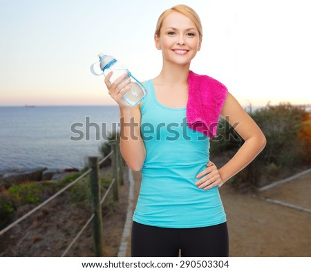 people, sport, fitness, jogging and recreation concept - happy woman with bottle of water and towel over beach sunset background - stock photo