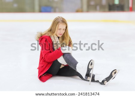 people, sport, trauma, pain and leisure concept - young woman fell down on skating rink and holding to her knee - stock photo