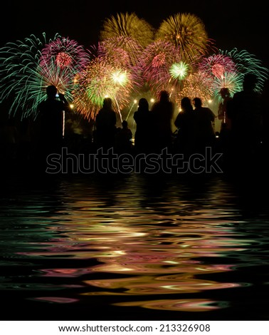 people stand watching for firework shows. digital compositing, colour tone, water reflection and ripple effects. - stock photo