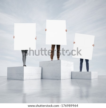 People standing on cubes and holding blank posters - stock photo