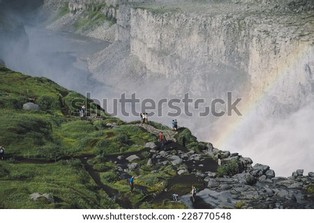people standing on the edge of a rock by the huge powerful waterfall and looking at the rainbow - stock photo