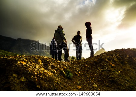 People standing on the top of a mountain, taking a hike. More mountains can be seen in the background. - stock photo