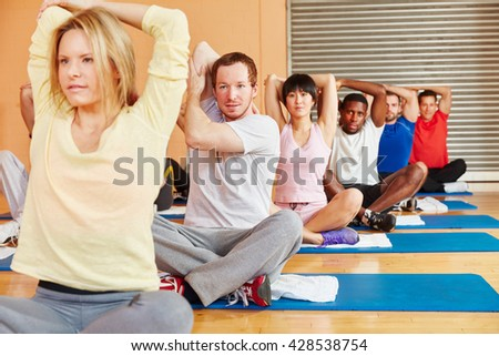 People stretching during fitness class in fitness center - stock photo