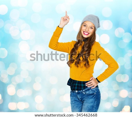 people, style and fashion concept - happy young woman or teen girl in casual clothes and hipster hat pointing finger up over blue holidays lights background - stock photo