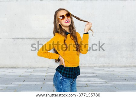 people, style and fashion concept - happy young woman or teen girl in casual clothes and sunglasses over urban street background - stock photo