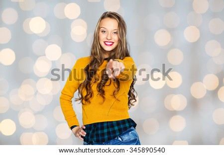 people, style and fashion concept - happy young woman or teen girl in casual clothes pointing finger on you over holidays lights background - stock photo