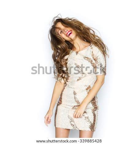 people, style, holidays, hairstyle and fashion concept - happy young woman or teen girl in fancy dress with sequins and long wavy hair dancing at party - stock photo