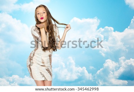 people, style, holidays, hairstyle and fashion concept - happy young woman or teen girl in fancy dress with sequins and long wavy hair sending blow kiss over blue sky and clouds background - stock photo