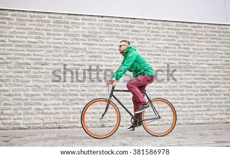 people, style, leisure and lifestyle - young hipster man riding fixed gear bike on city street over brick wall background - stock photo
