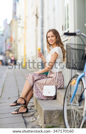 people, style, technology, leisure and lifestyle - happy young hipster woman with fixed gear bike eating ice cream on city street - stock photo