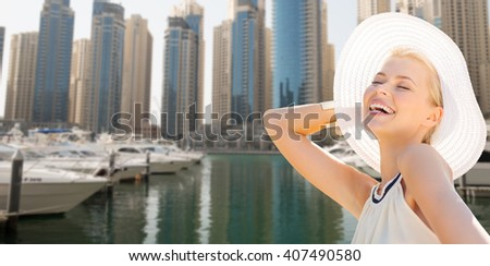people, summer holidays, travel, tourism and vacation concept - happy beautiful woman in sun hat enjoying summer over dubai city waterfront and boats background - stock photo