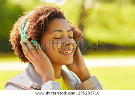 people, summer, technology and leisure concept - happy african american young woman face with headphones listening to music outdoors - stock photo