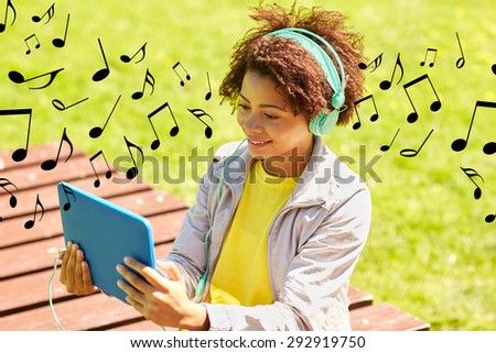people, summer, technology and leisure concept - happy african american young woman in headphones with tablet pc computer listening to music or watching video outdoors over notes background - stock photo