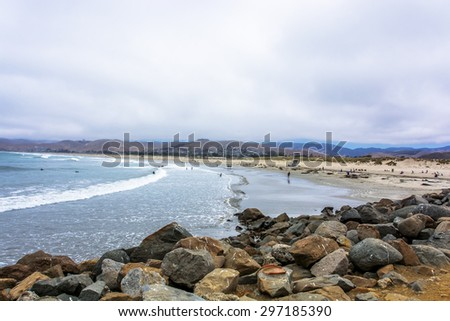 People sunbathing, surfing, & swimming near Majestic Morro Rock overlooking the Pacific Ocean, next to Morro Strand state beach, on the California Central Coast, near Cambria, CA. - stock photo