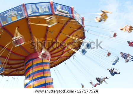 People swing past with motion blur, shot to convey some of the excitement of the midway ride. - stock photo