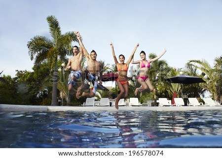 people taking a rest at swimming pool in resort - stock photo