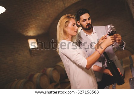 People tasting red wine in winery basement