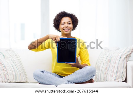 people, technology, advertisement and leisure concept - happy african american young woman sitting on sofa and showing tablet pc computer black blank screen at home - stock photo