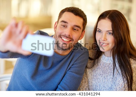 people, technology and dating concept - happy couple taking smartphone selfie at cafe or restaurant