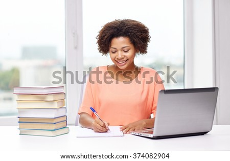 people, technology and education concept - happy african american young woman sitting at table with laptop computer and books at home - stock photo