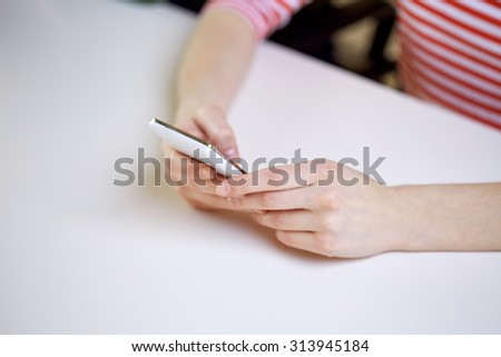 people, technology and internet concept - close up of teenage girl hands with smartphone at home - stock photo