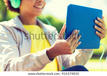 people, technology and leisure concept - close up of happy african american young woman with tablet pc computer and headphones listening to music outdoors - stock photo