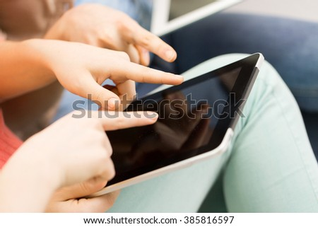 people, technology and leisure concept - close up of young women with tablet pc computer at home