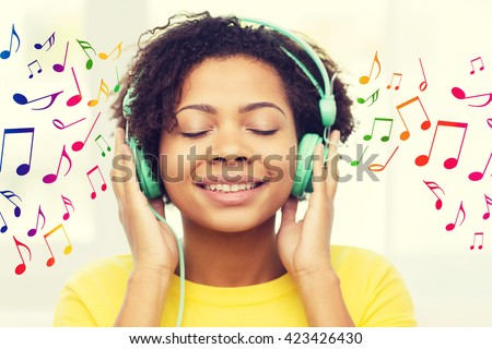 people, technology and leisure concept - happy african american young woman sitting on sofa with headphones listening to music over notes background - stock photo