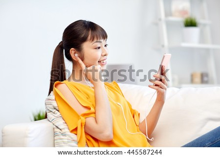 people, technology and leisure concept - happy asian young woman sitting on sofa with smartphone and earphones listening to music at home