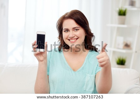 people, technology, communication and leisure concept - happy young plus size woman sitting on sofa and showing smartphone blank screen and showing thumbs up at home