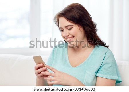 people, technology, communication and leisure concept - happy young plus size woman sitting on sofa with smartphone at home