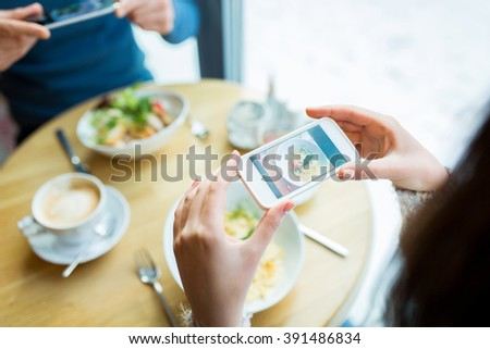 people, technology, eating and dating concept - close up of couple with smartphones picturing food at cafe or restaurant - stock photo
