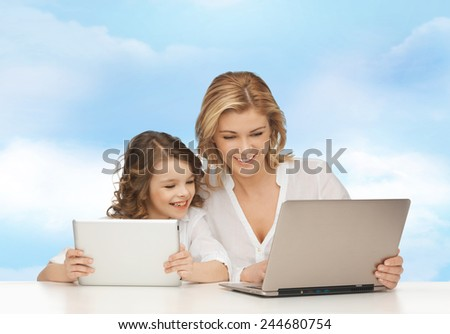 people, technology, family and parenthood concept - happy mother and daughter with laptop and tablet pc computers sitting at table over blue sky background