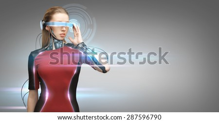 people, technology, future and progress - young woman with futuristic glasses and microchip implant or sensors over gray background with virtual projection and laser light - stock photo
