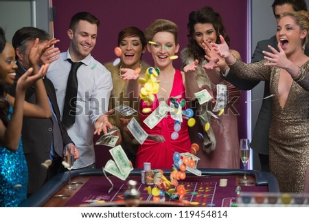 People throwing chips and cash on roulette table in casino - stock photo