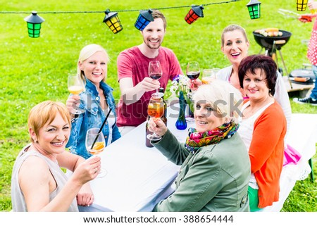 People toasting at party, in the background man at bbq grill with beer bottle in hand - stock photo