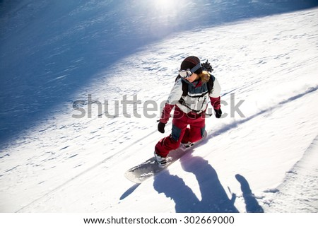 people tourists descend on a skateboard on snow-covered mountain - stock photo