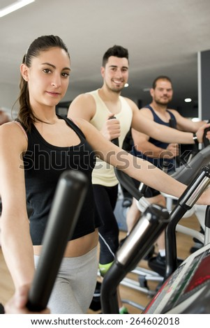 People training at cross trainer elliptical bike looking at the view