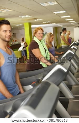 People training in gym, using running machine.