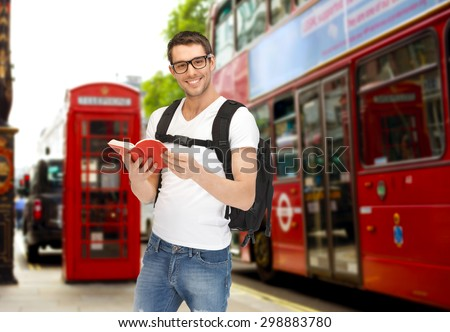 people, travel, tourism and education concept - happy young man with backpack and book over london city city bus on  street background - stock photo