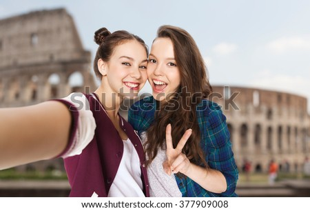 people, travel, tourism and friendship concept - happy smiling pretty teenage girls taking selfie and showing peace sign over coliseum in rome background