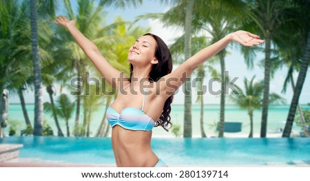 people, travel, tourism and summer concept - happy young woman in bikini swimsuit with raised hands looking up over swimming pool and beach with palm trees background - stock photo