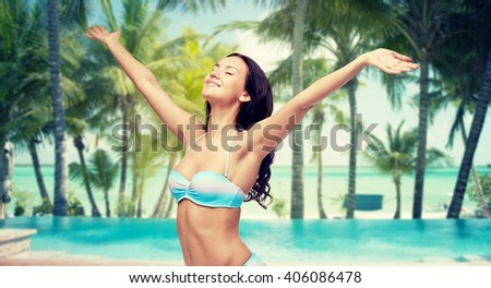 people, travel, tourism and summer concept - happy young woman in bikini swimsuit with raised hands looking up over swimming pool and beach with palm trees background