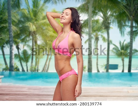 people, travel, tourism and summer concept - happy young woman posing in pink bikini swimsuit over swimming pool and beach with palm trees background - stock photo