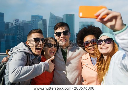people, travel, tourism, friendship and technology concept - group of happy teenage friends taking selfie with smartphone and showing thumbs up over singapore city background - stock photo